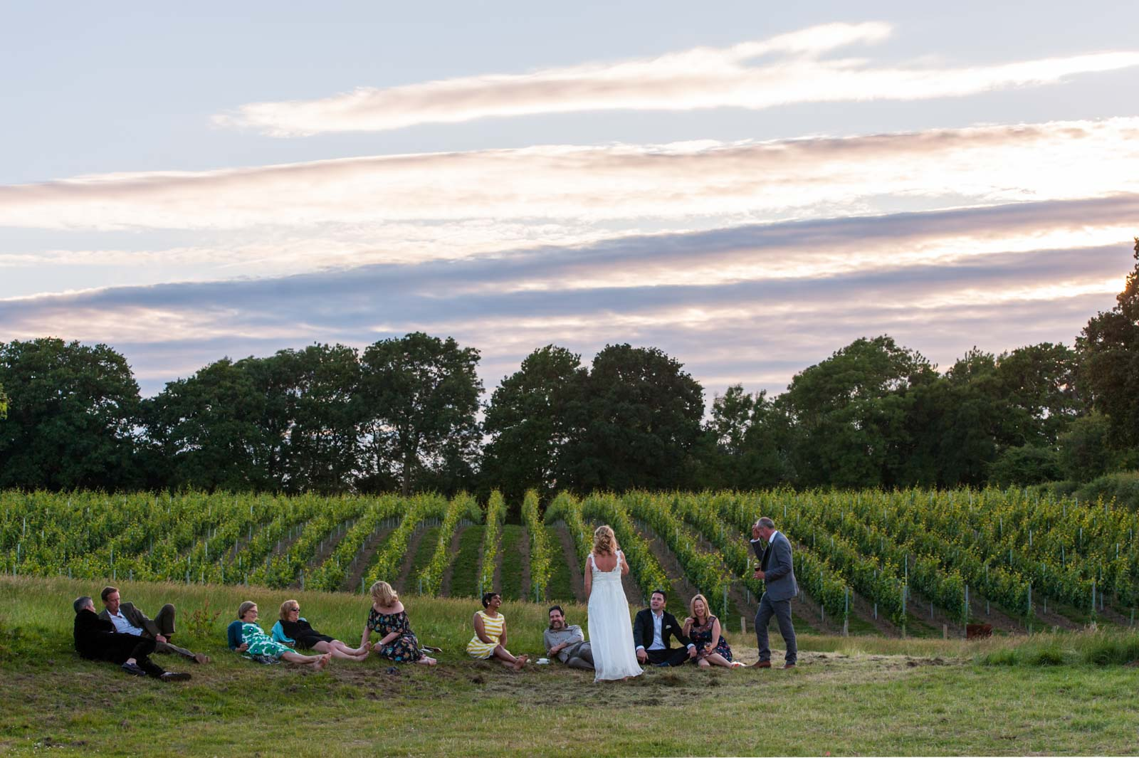 Bride and guests relaxing in a field at Court Gardens Farm wedding