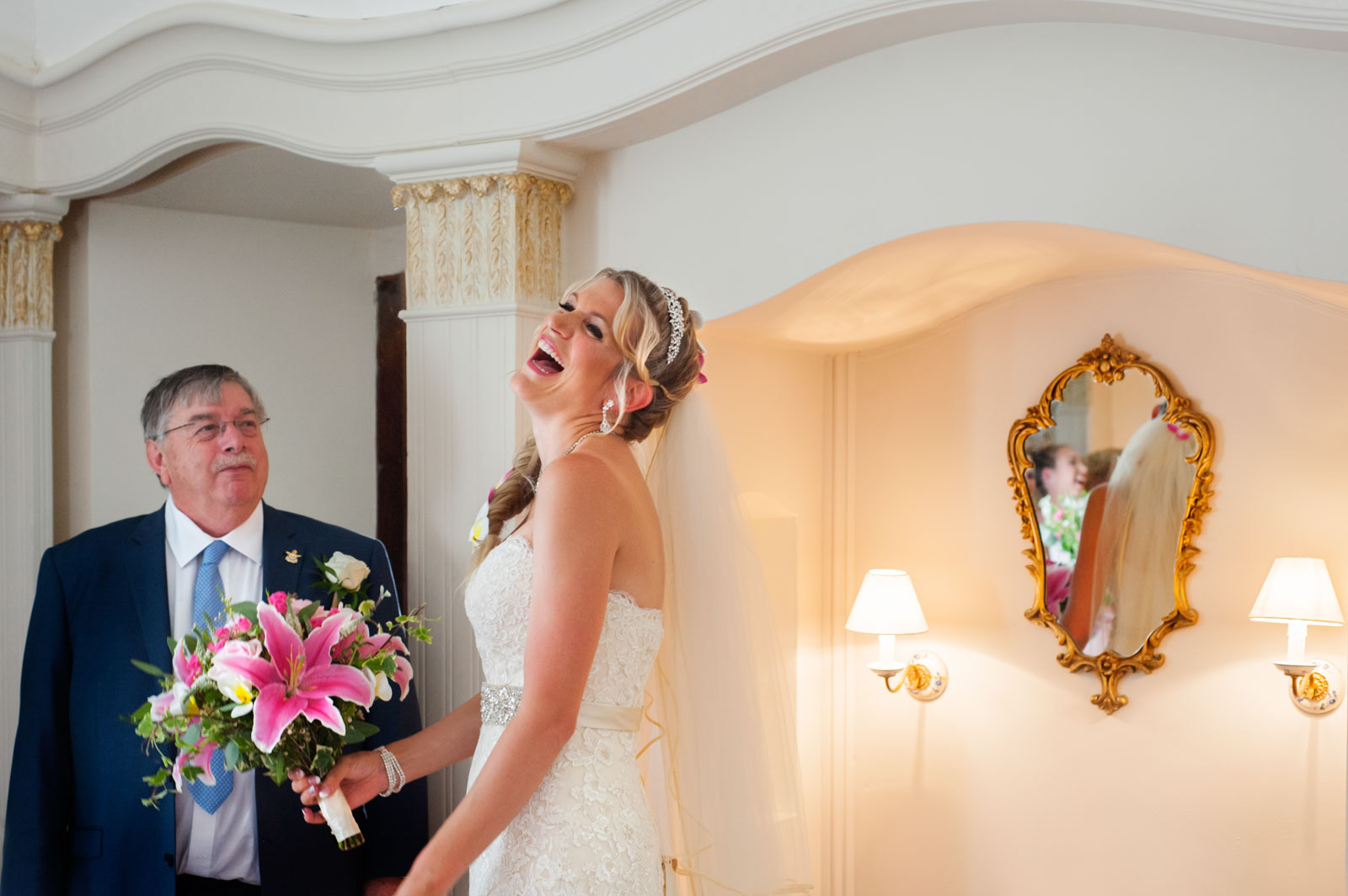 Bride laughing with father before wedding at Hayne House