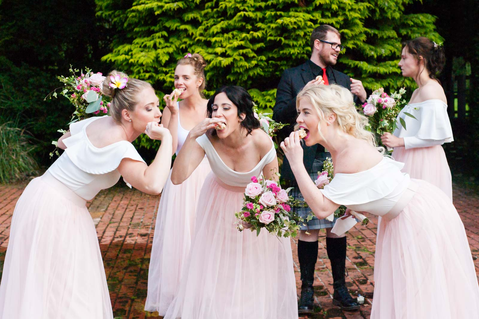 Bridesmaids being silly with cakes