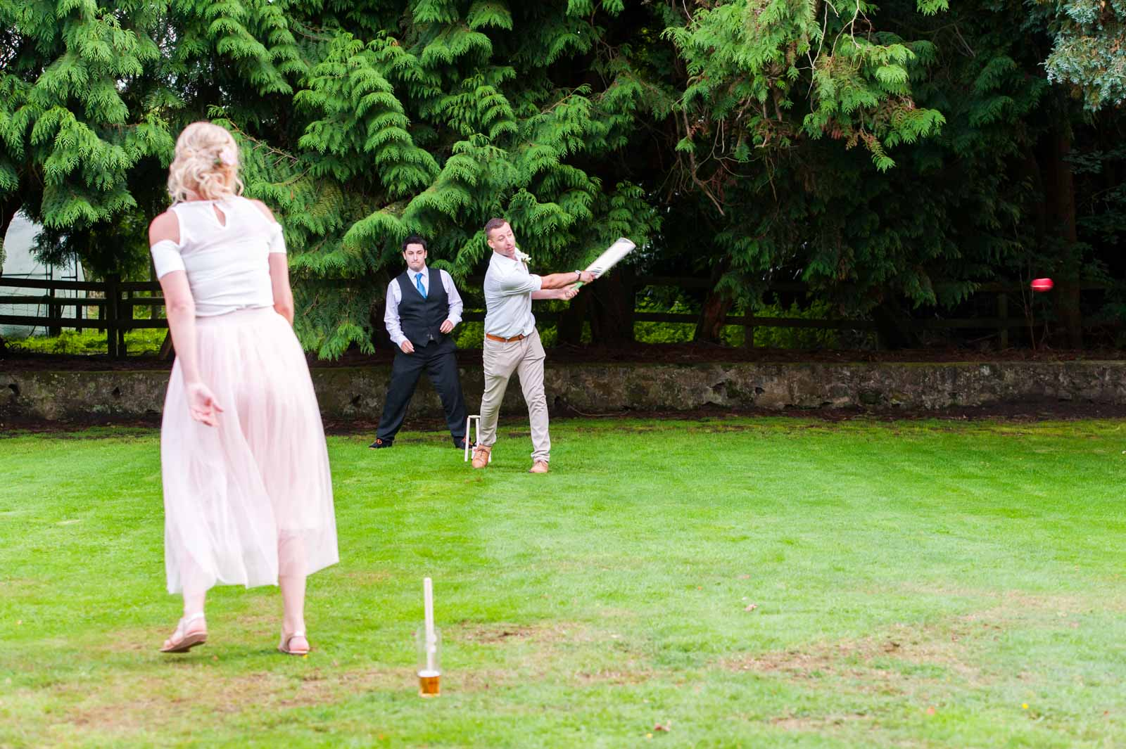 Wedding guests playing cricket