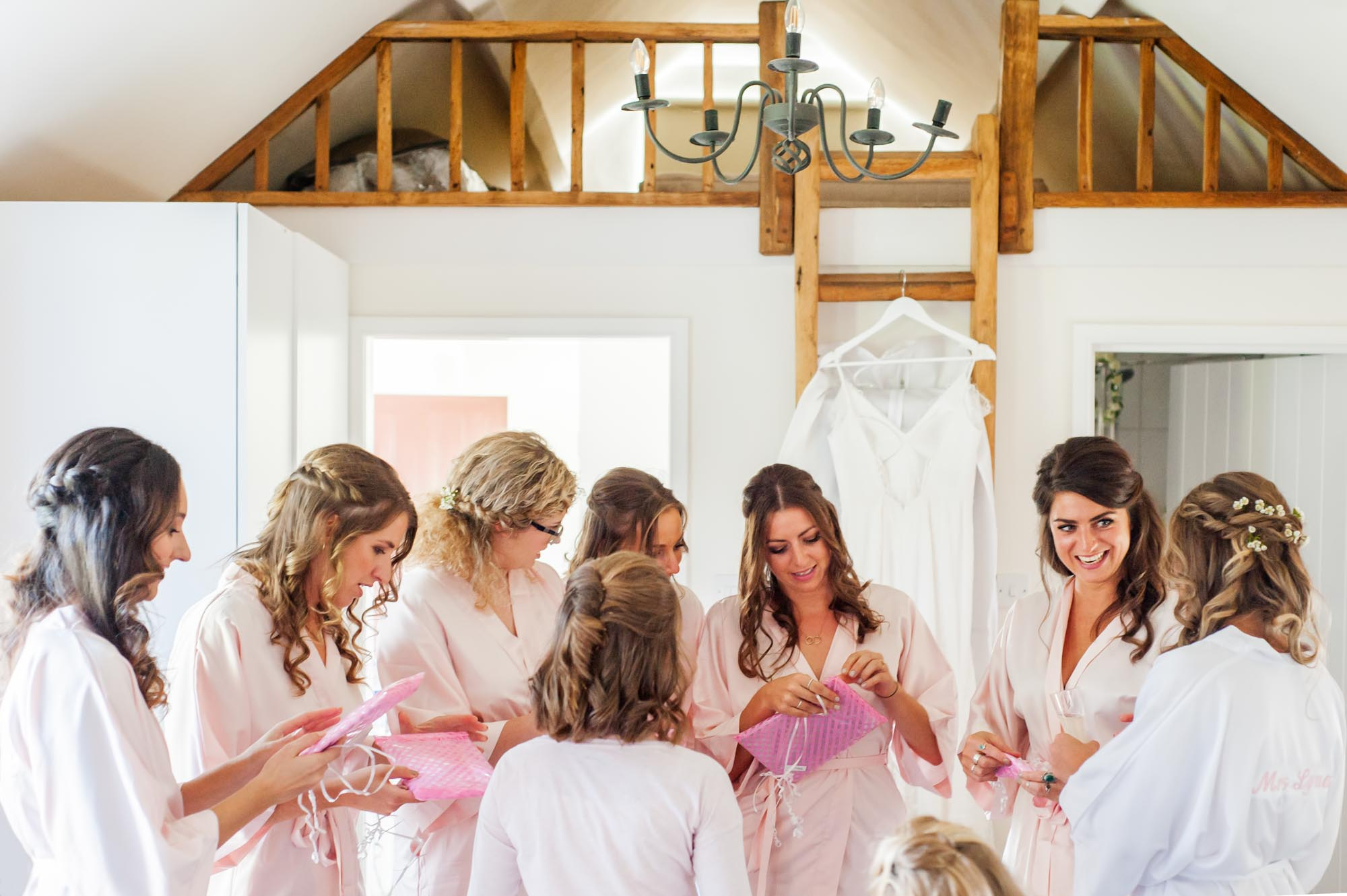 Bride and bridesmaids opening presents whilst getting ready