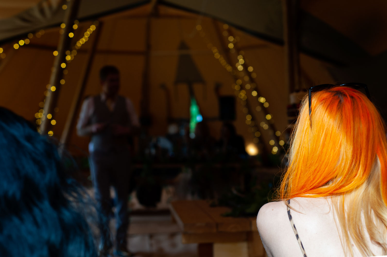 Light on a womans orange hair looking into wedding marquee by alternative sussex wedding photographer James Robertshaw