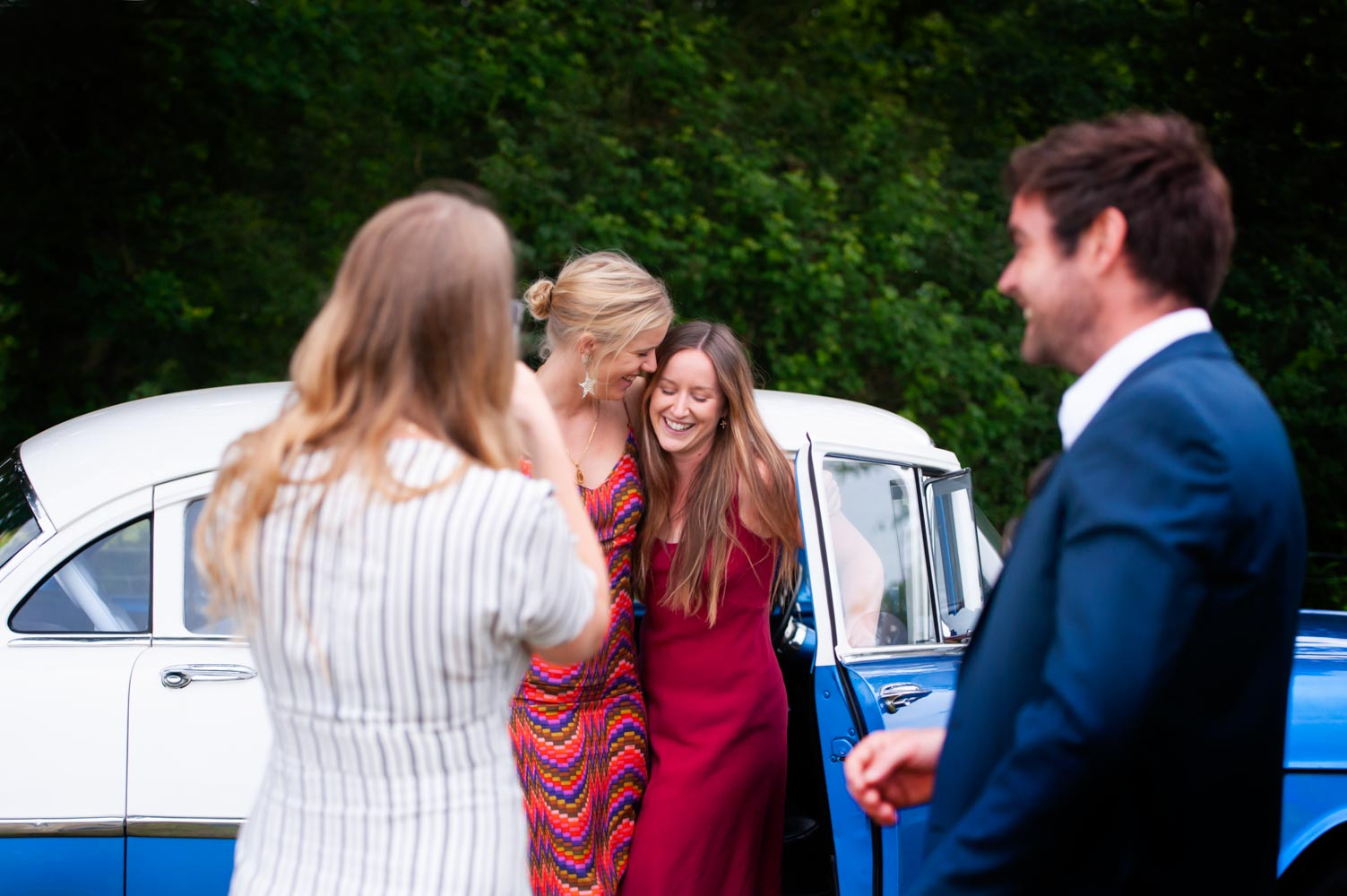 Wedding guests posing with a car for pictures