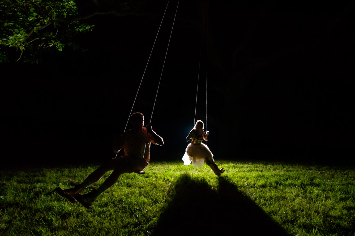 Wedding couple on swings at night