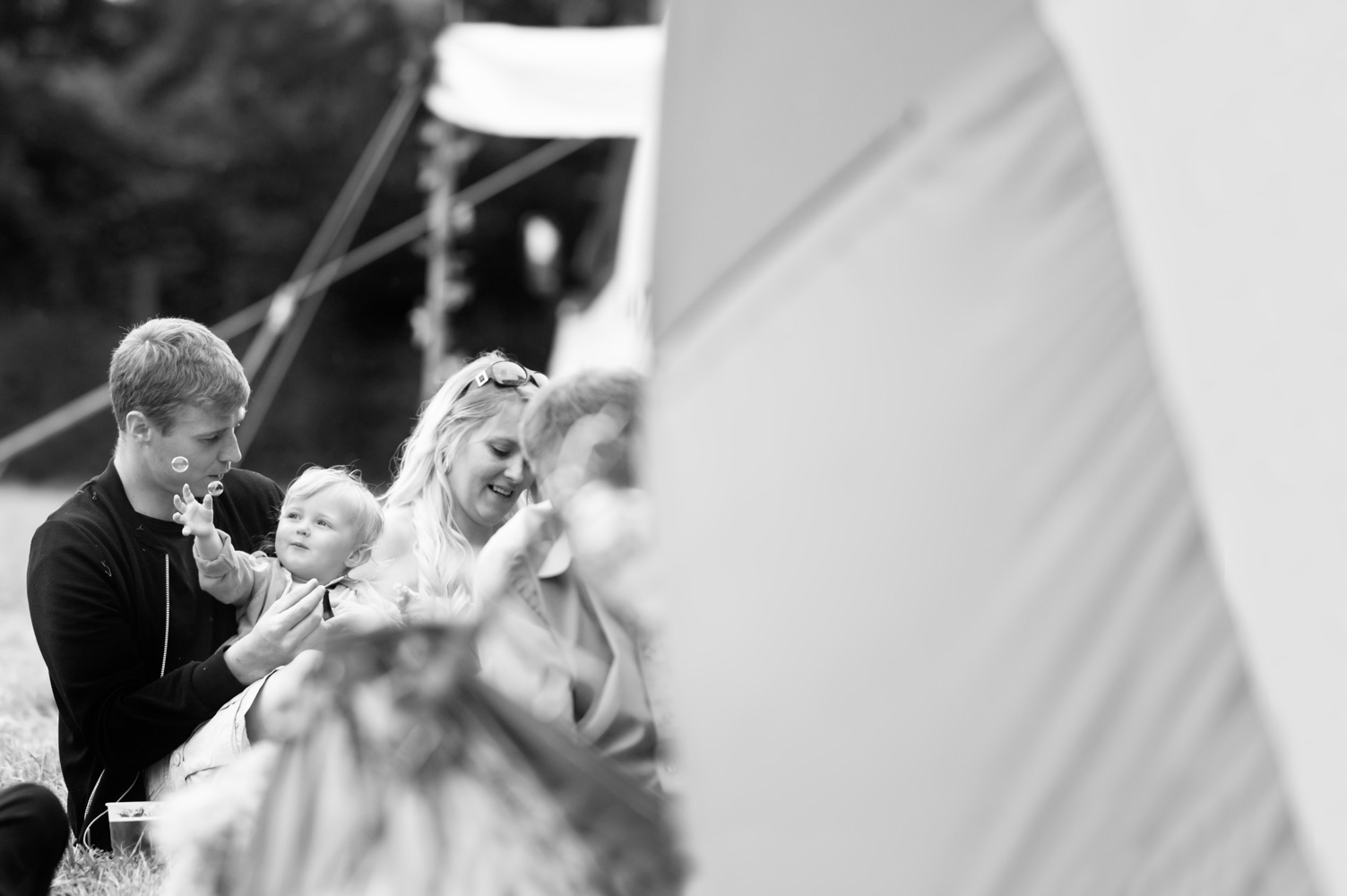 Family outside tent at wedding by alternative sussex wedding photographer James Robertshaw