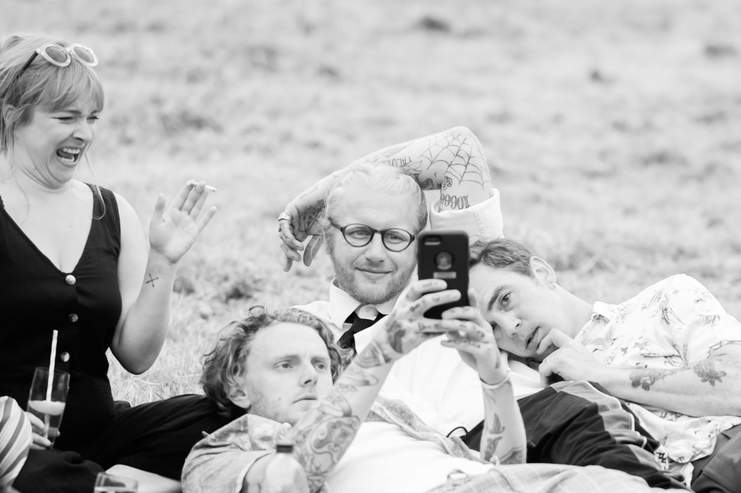 Relaxed wedding guests looking at a phone by alternative sussex wedding photographer James Robertshaw