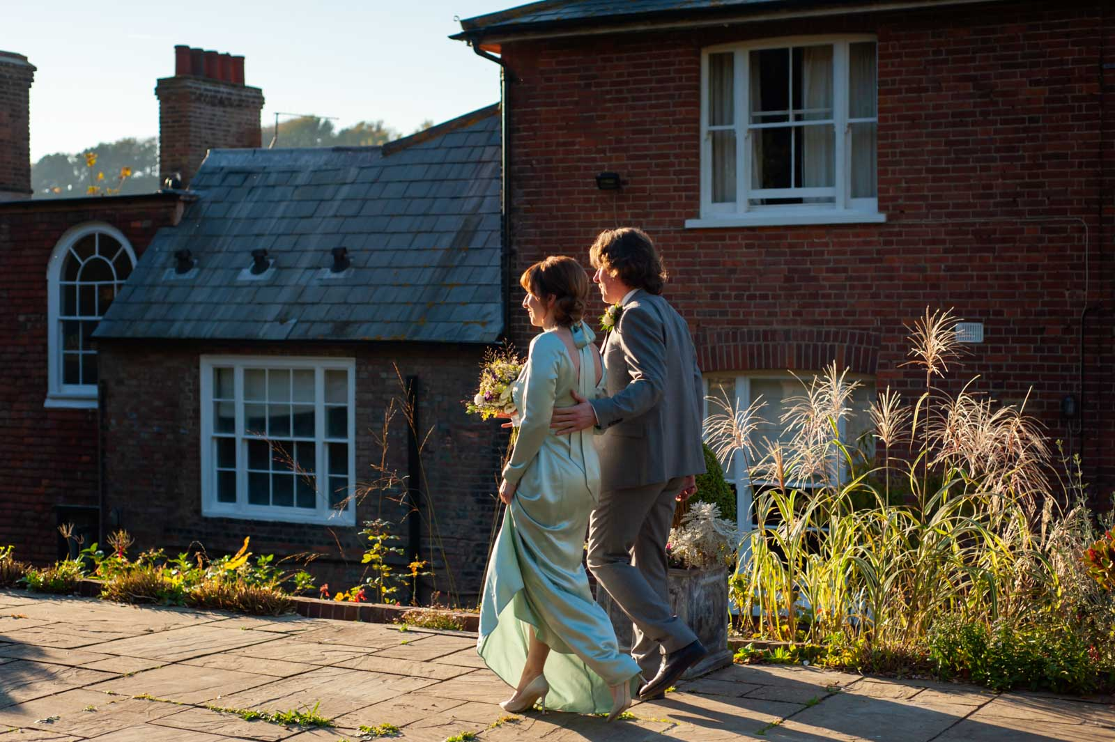 Bride and walking to outdoor cermeony in autumn light