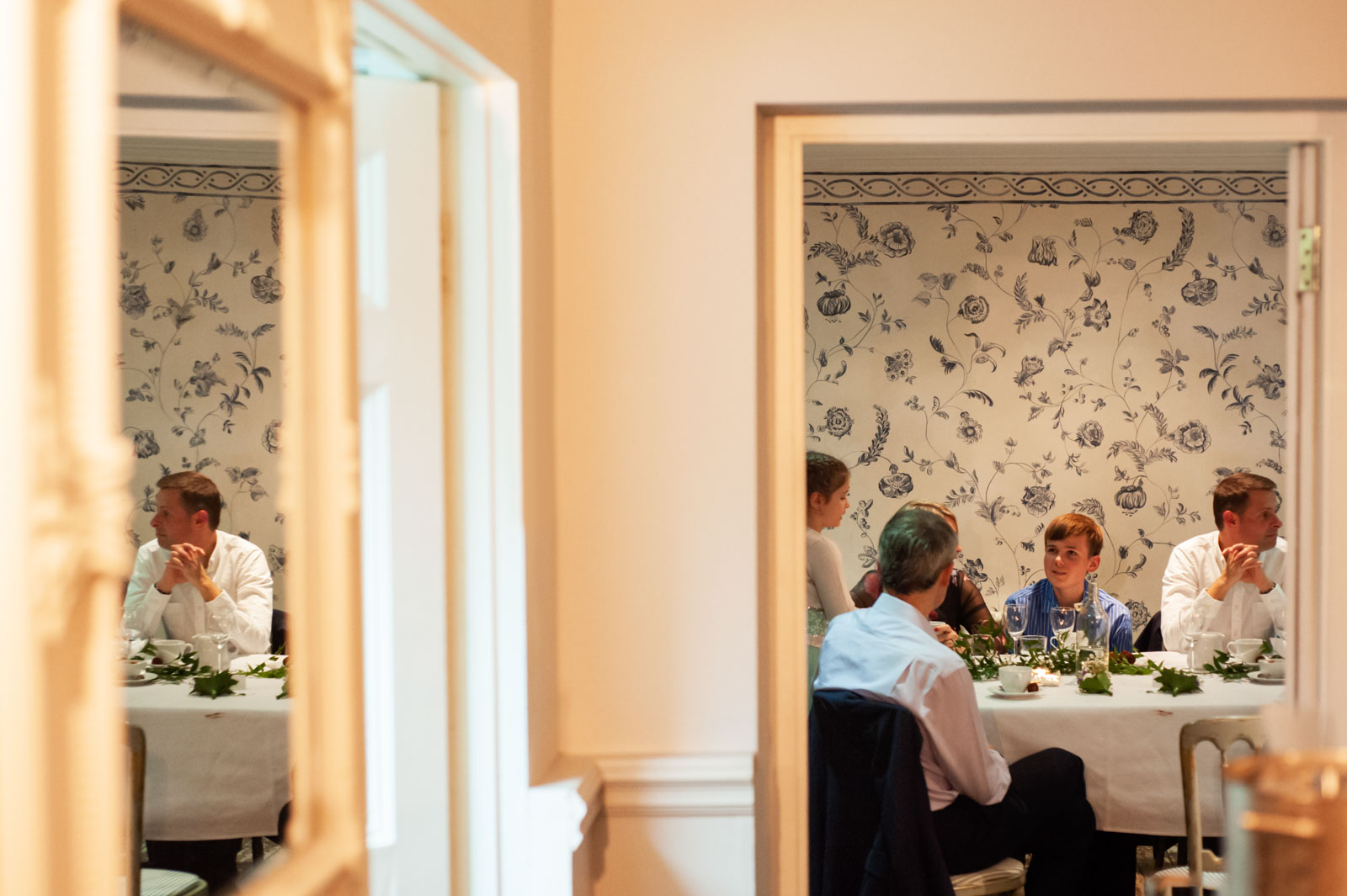 Wedding guests at table reflected in mirror