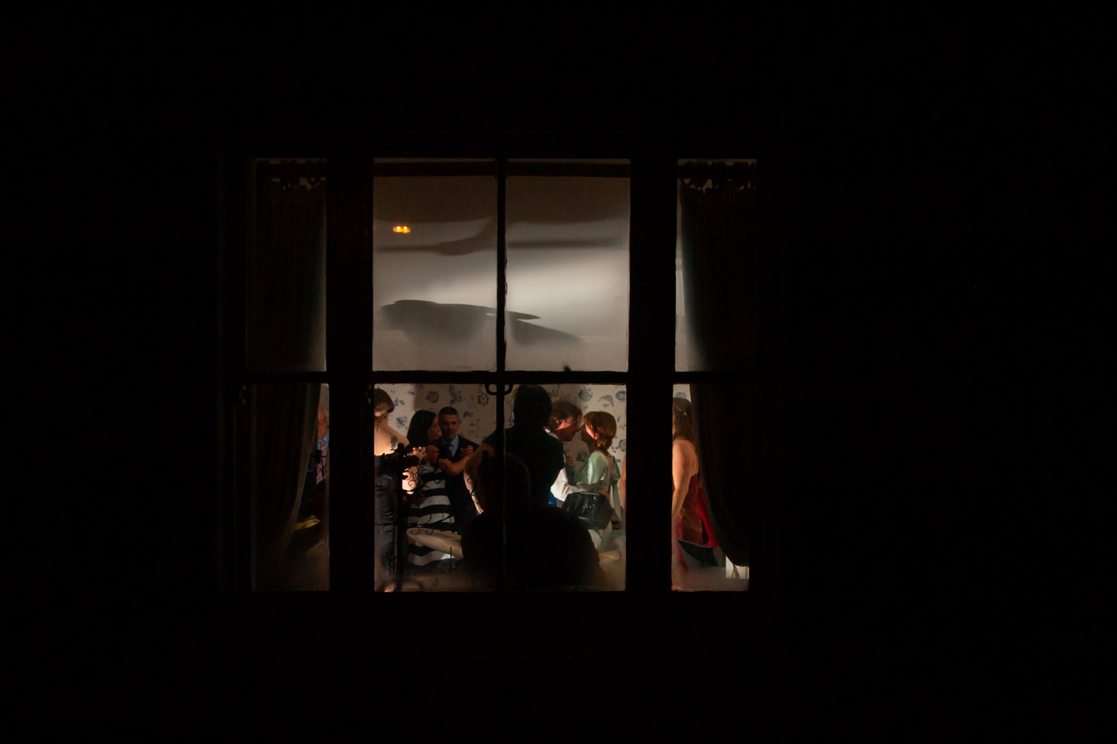 Looking through window at couple and guests dancing