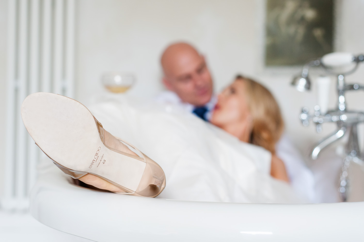 Close up Bride's Jimmy Choo shoe whilst lying in bath with husband at the Old Rectory Hastings