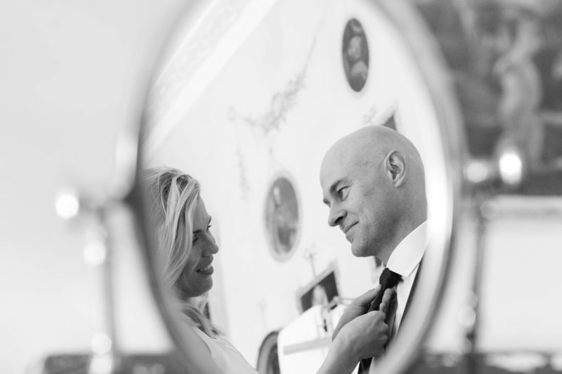 Bride adjusting Groom's tie reflected in mirror