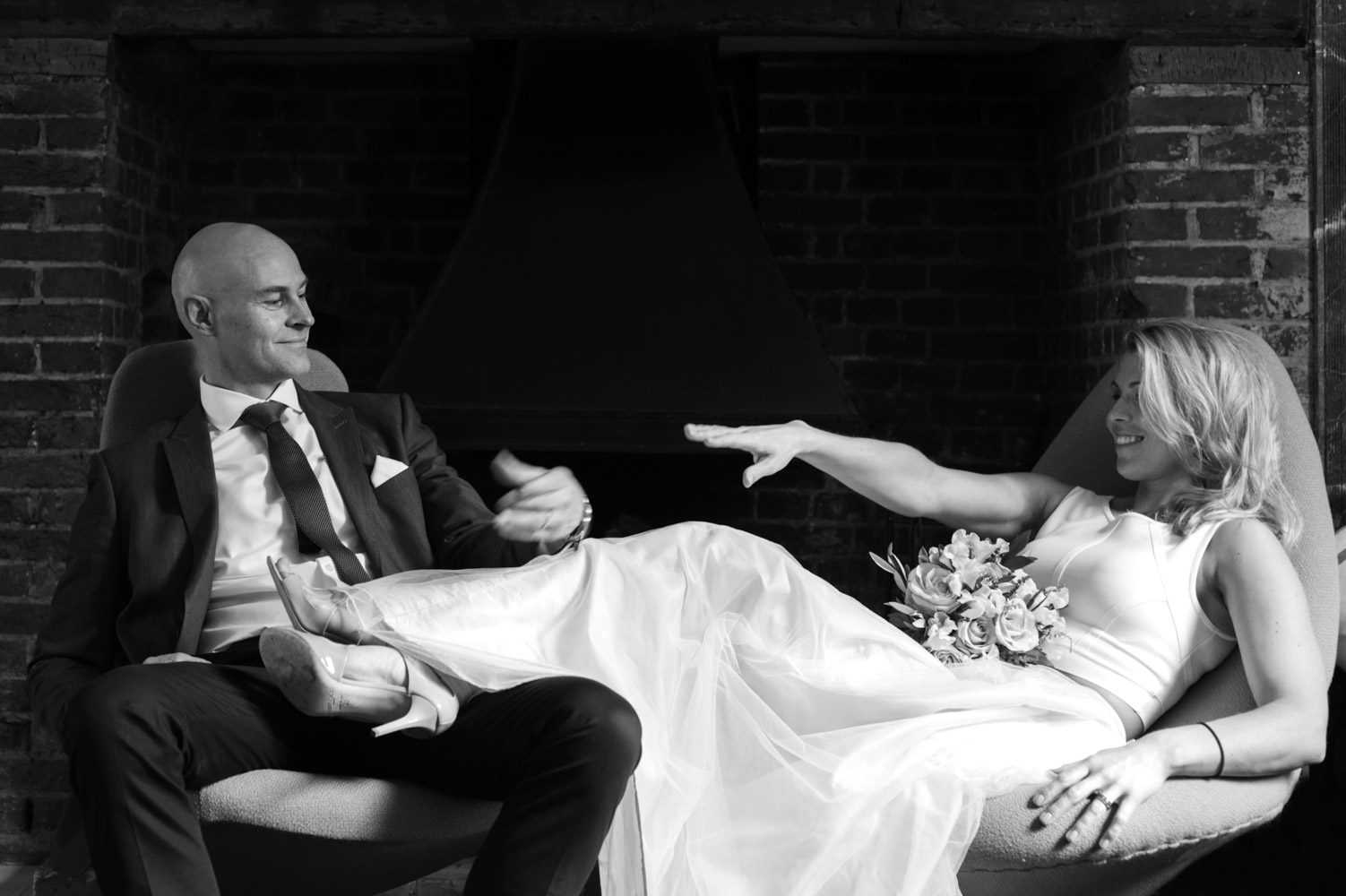 Bride sitting legs across groom offerring her hand at the Old Rectory Hastings