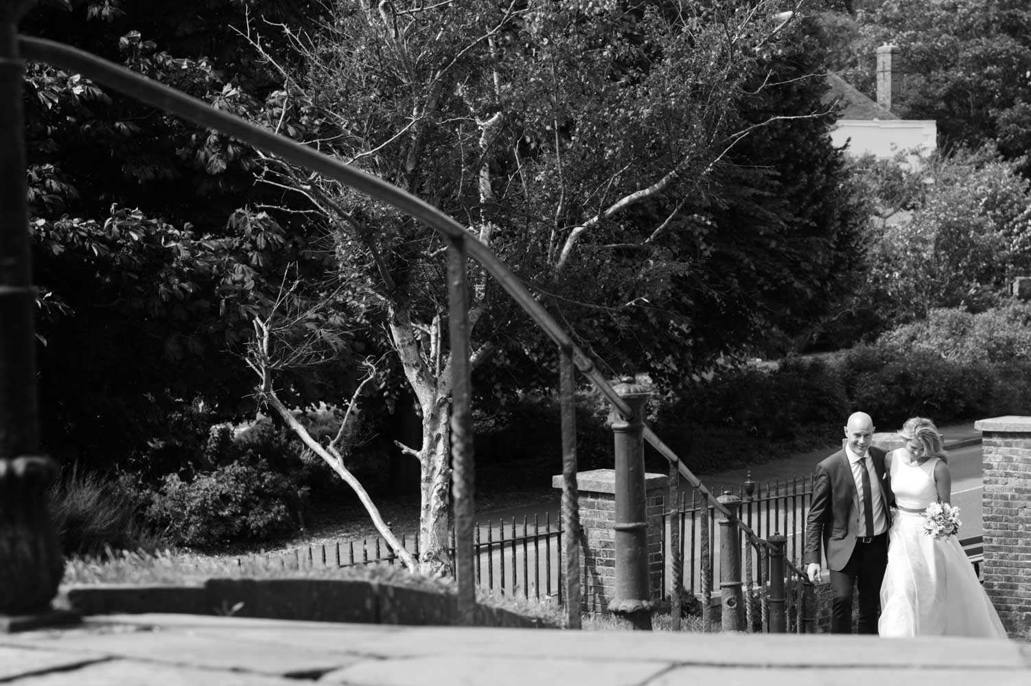 Couple walking up church steps in Hastings